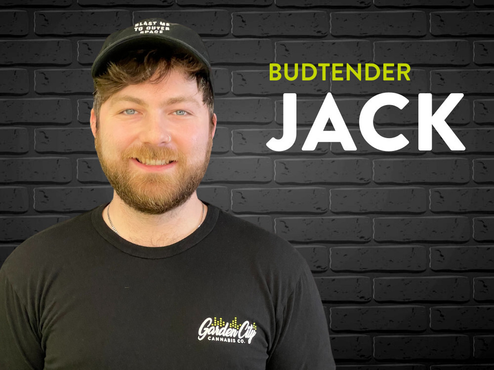Employee Jack standing against a black brick background.